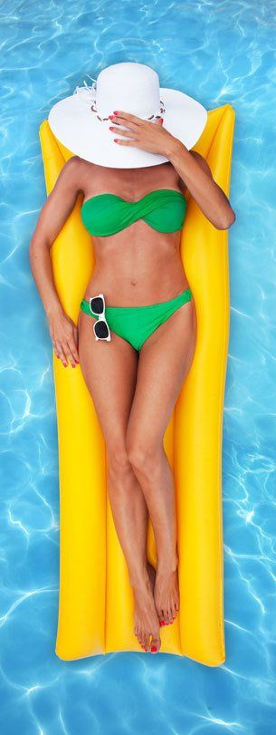 A lady in a jade green bikini with her face covered by a white sunhat, lying on a yellow lilo in a pool
