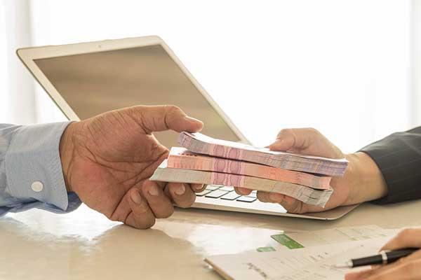 una mano sta consegnando a un'altra una serie di banconote in un ufficio