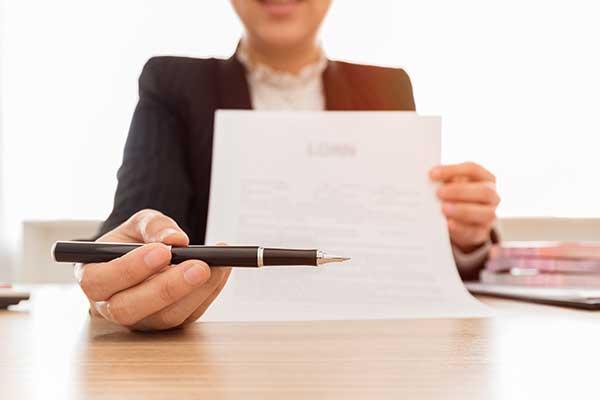 una donna con un completo nero seduta a una scrivania sta consegnando a una persona un foglio da firmare
