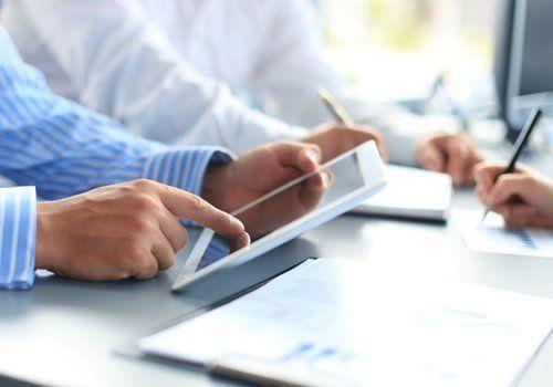 persone scrivono e digitano sul tablet durante una riunione