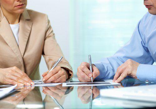 due persone scrivono durante una riunione