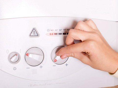 mano che sistema i gradi di una caldaia tramite una manopola