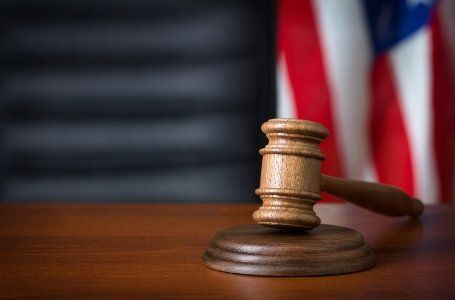 A gavel rests on a table in front of an American flag