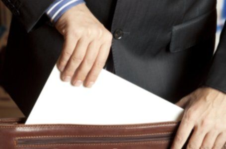A lawyer pulls documentation from his briefcase