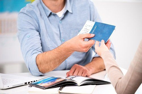 Lavoratrice dando il passaporto con un biglietto a un cliente
