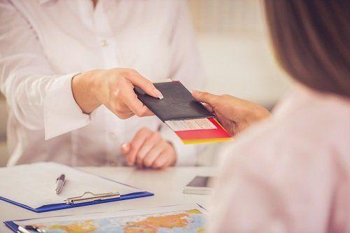 Impiegata dando il passaporto con un ticket a una giovane
