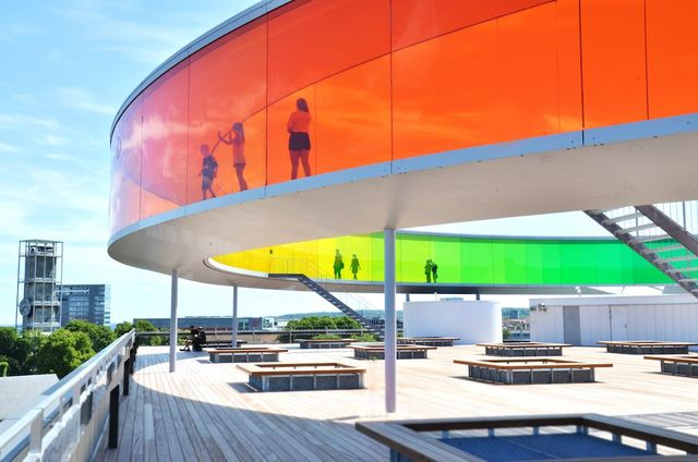 A rainbow colored art installation of Oafur Eliasson in Aarhus, orange in the foreground.