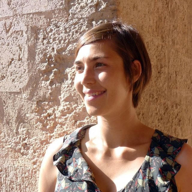 A portrait of Carina Kurta in front of a light stone wall.