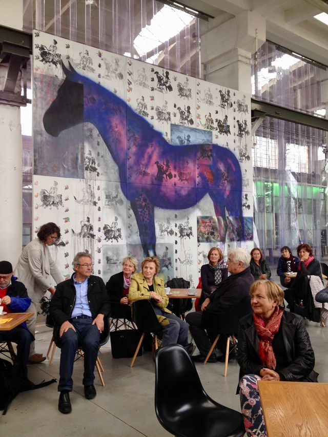 A group of people in a room, listening to a conference, in the background a huge poster showing a violet horse.