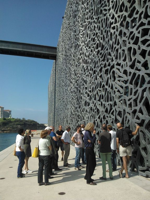 A group of people standing in front of the concrete facade of the museum MUCEM in Marseille.
