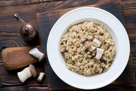 Piatto di riso con funghi coltivati su una tavola di legno ,vari funghi freschi al lato