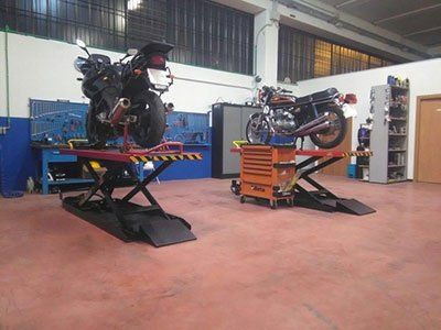 vista interna di officina con motociclette in riparazione