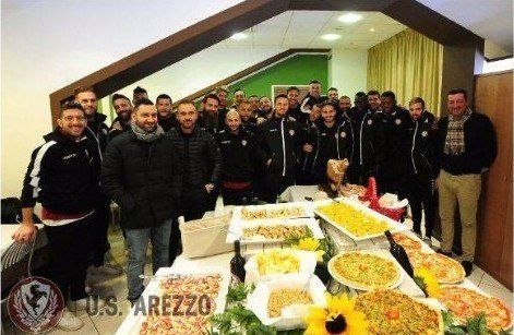 a squadra di calcio  dell'Arezzo in un ristorante con un buffet di pizze