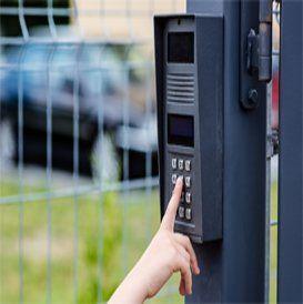 persona spinge i pulsanti di  un videocitofono