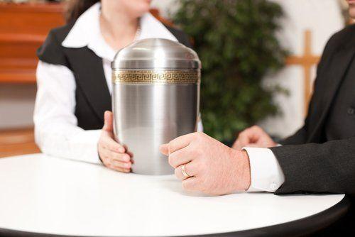 due persone toccano un vaso cinerario