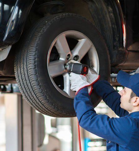 A mechanic fitting car tyre