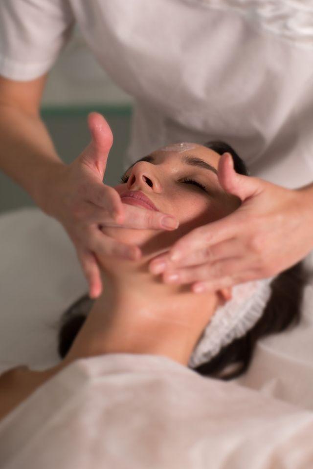 mani massaggiano la fronte di una cliente stesa sul lettino
