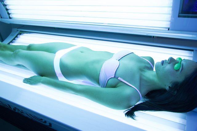mani con guanti mentre utilizzano un dispositivo laser  sul corpo di una donna