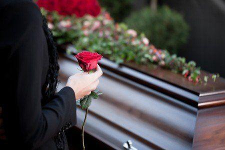 la mano di una donna con una rosa rossa e davanti una bara