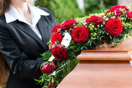 una donna davanti a una corona di rose rosse su una bara