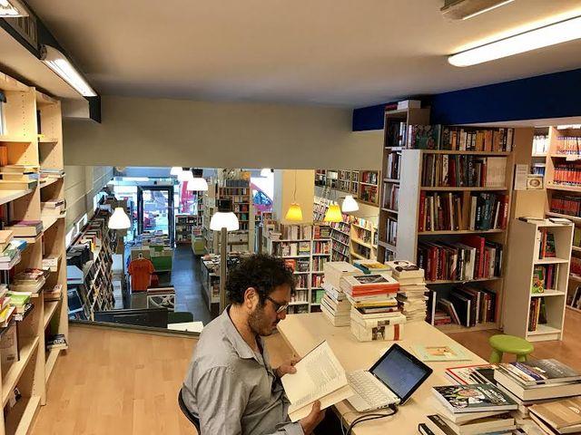 un uomo seduto sulla sedia con un libro in una libreria