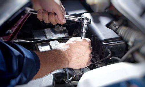 meccanico con un attrezzo sta riparando un motore - autofficina 2A - Verona