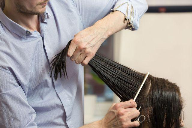 Un uomo mentre taglia capelli di una donna con un forbice