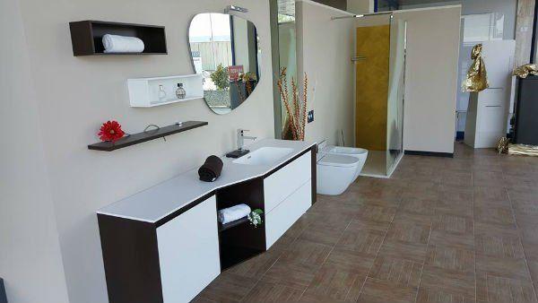 un mobile da bagno di colore bianco e marrone e uno specchio a muro