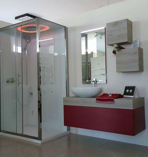 un box doccia e un mobiletto bordeaux e grigio con sopra un lavabo