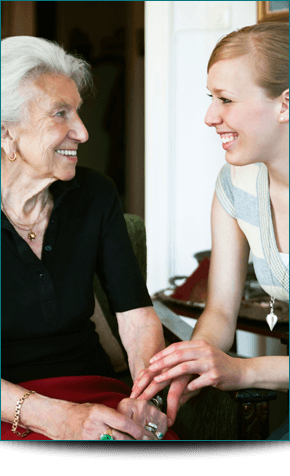 A young woman talking to an elderly lady and smiling