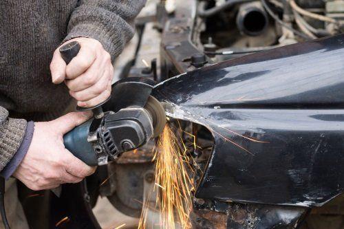 due mani con un flessibile al lavoro sulla carrozzeria di un'auto