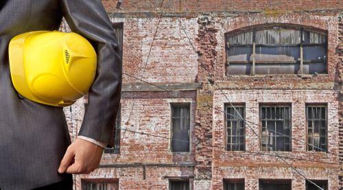 un uomo con un casco da cantiere con un palazzo da ristrutturare sullo sfondo