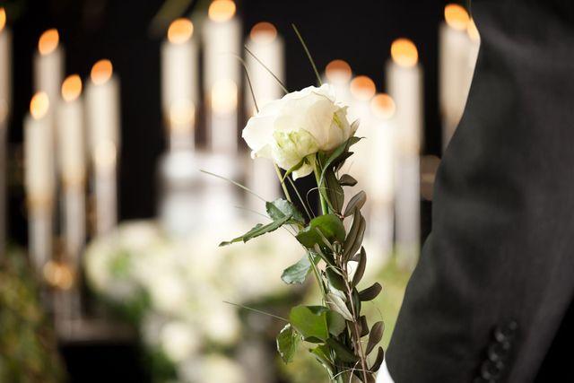 una braccio e una mano che tiene in mano una rosa bianca e davanti delle candele accese
