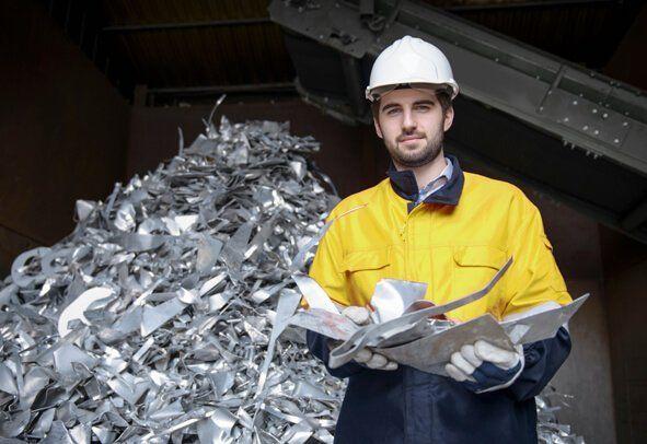 A yard worker holding scrap metal