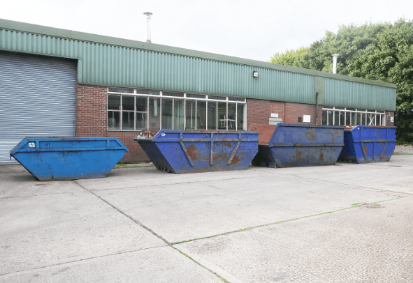 A row of skips outside a commercial building
