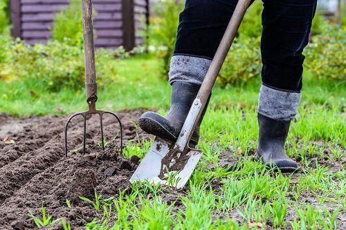 inquadratura dei piedi di un giardiniere con stivali di gomma che spingono una vanga nel terreno