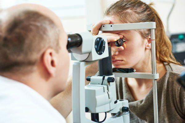 un oculista mentre fa un esame visivo a una donna
