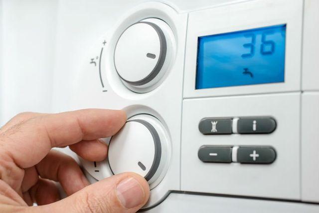 due dita che regolano un termostato da una manopola