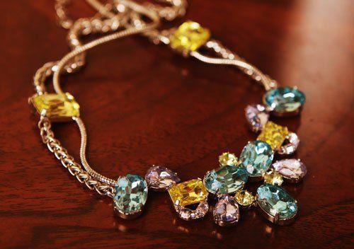 una collana con pietre di color azzurro viola e giallo