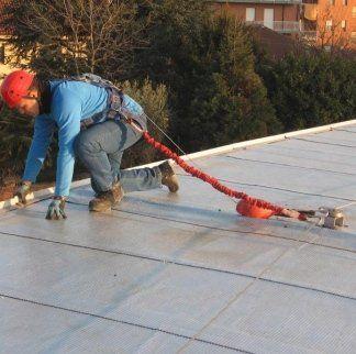 operaio mentre installa linee vita sul tetto