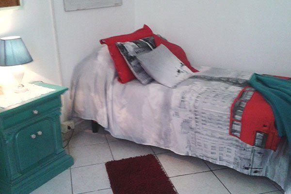 una stanza con un comodino verde e un letto singolo