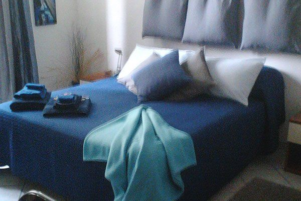 una stanza con un letto matrimoniale blu
