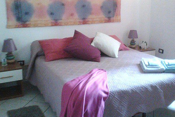 una camera con un letto matrimoniale rosa e due comodini con due lampade ai lati