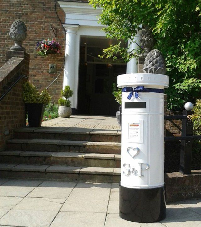 White pillar post box at the foot of four stone steps