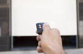 Primo piano di una mano che preme il telecomando per aprire la porta di un garage