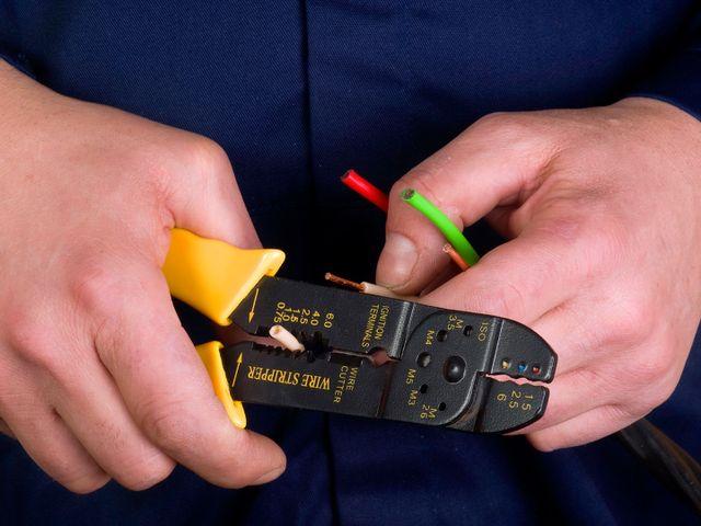 Primo piano di una pinza da elettricista mentre trancia dei cavetti elettrici