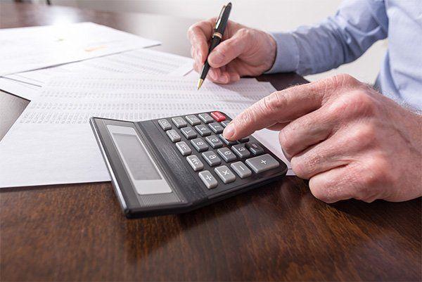 un uomo con in mano una penna mentre usa una calcolatrice e dei fogli