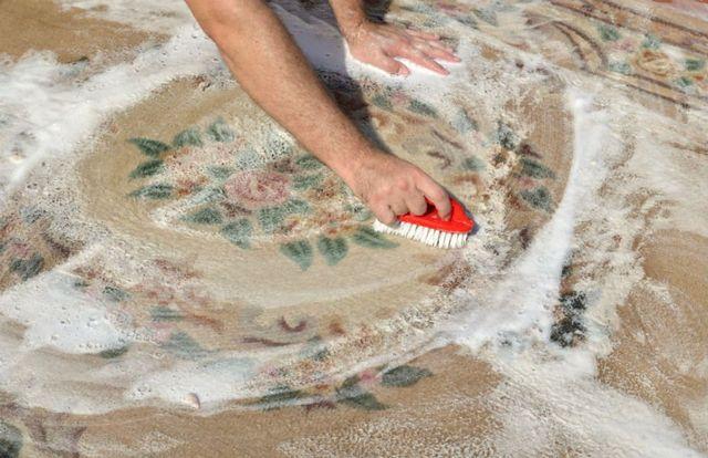 una mano con una spazzola mentre pulisce un tappeto