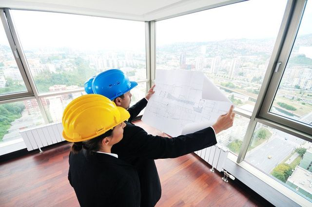 Male and female architects in hard hats, in the corner of a building with city view, looking at a plan