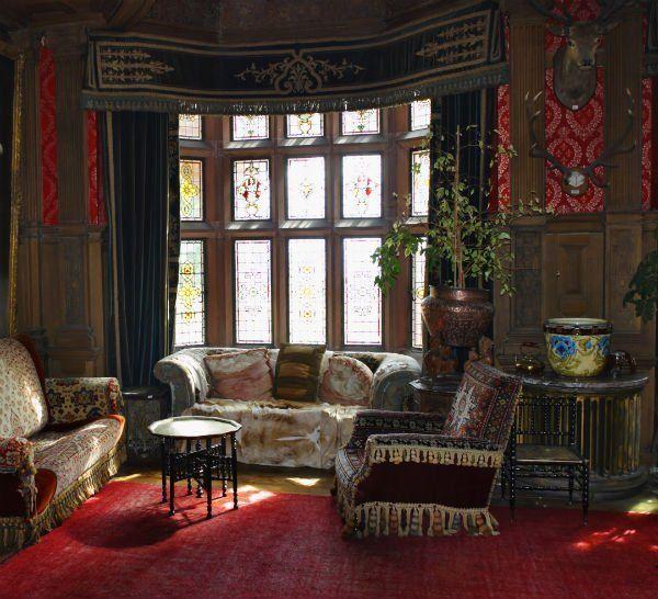 un divano, due poltrone antiche e un tappeto rosso sul pavimento